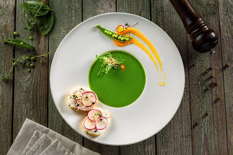 Healthy pea cream soup in a rim soup plate. Delicious European cuisine meal.